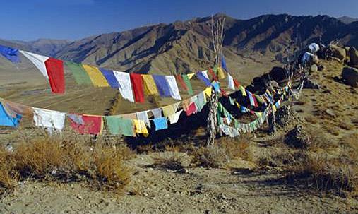 דגלי תפילה טיבטיים תלויים לאורך דרך הררית בנפאל.